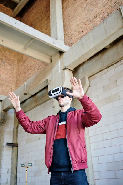 Premium Photo Young Engineer In Vr Headset Standing Inside Unfinished Building And Looking At Virtual Example Of New House Or Other Construction