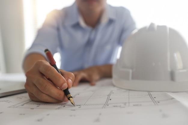 Молодые инженеры или архитектор, держащий ручку и план чертежа на светокопии на рабочем месте. Premium Фотографии