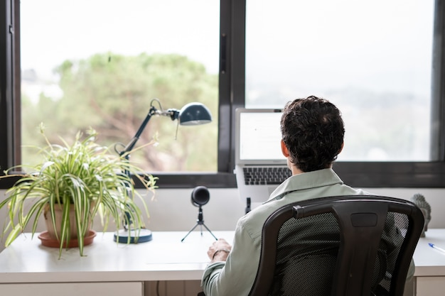 Young entrepreneur works from home in his office with the computer in front of a window Premium Photo