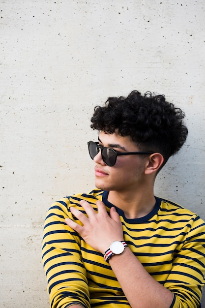 Young ethnic curly man in sunglasses and striped sweatshirt Free Photo