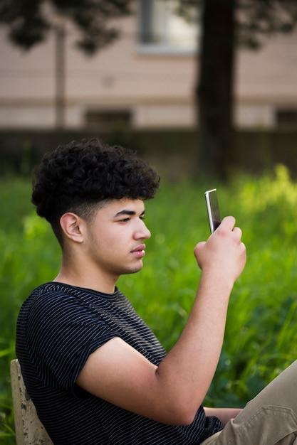 Young ethnic curly man taking photo on bench Free Photo