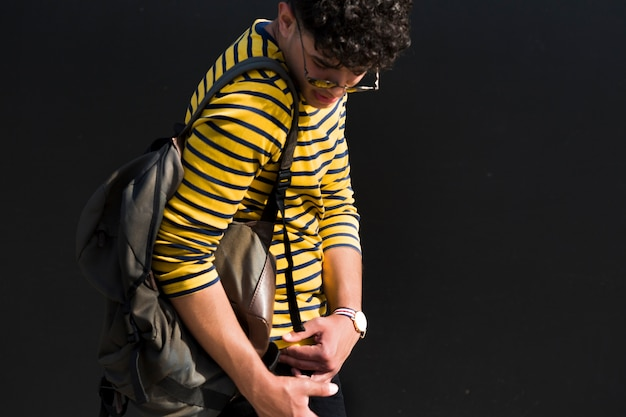 Young ethnic male with curly hair and backpack in striped shirt looking back down Free Photo