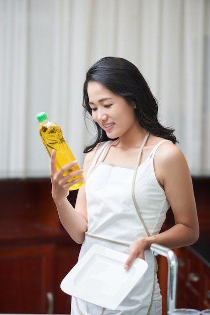 Young ethnic woman with detergent bottle at home Free Photo