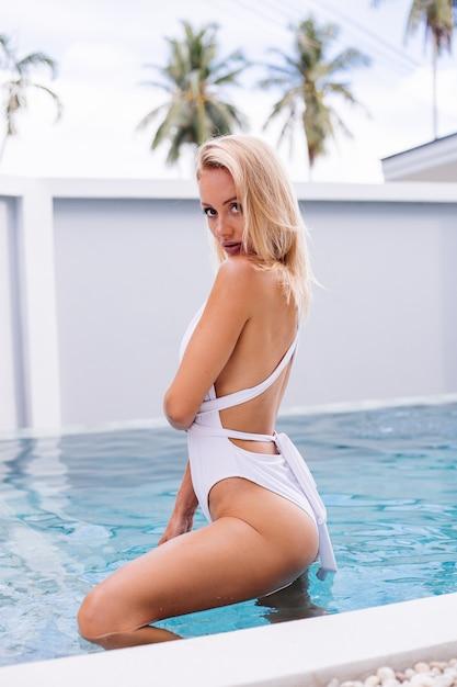 La giovane donna europea in forma di capelli biondi in costume da bagno bianco si trova in una piscina di colore azzurro, la luce naturale del giorno tiene la paglia di plastica di cocco Foto Gratuite
