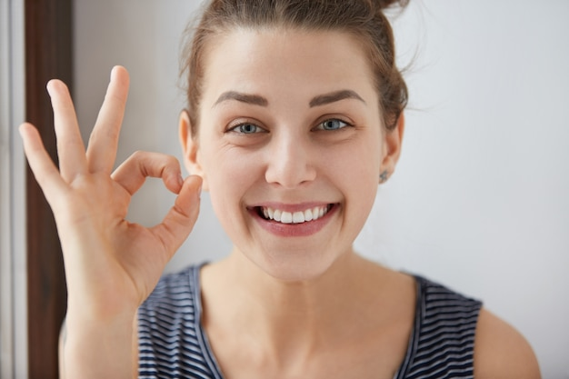 Young european brunette female showing ok-gesture with her fingers. happy woman in striped top smiling with blue eyes. her white-teeth mouth and happy face prove everything goes according to plan. Free Photo