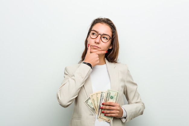 Young european business woman holding dollar banknotes looking sideways with doubtful and skeptical expression. Premium Photo