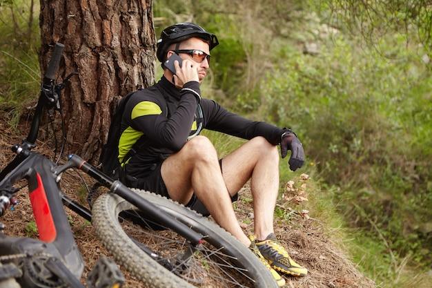 Giovane ciclista europeo in abiti sportivi che riposa nei boschi parlando al telefono cellulare Foto Gratuite