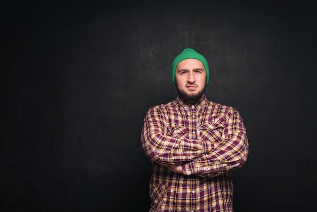 緑のニット帽をかぶったひげを持つ若いヨーロッパ人は、驚いて困惑しているように見えます。指を上向きと右側に表示します。黒の背景、テキストまたは広告用の空白のコピースペース Premium写真