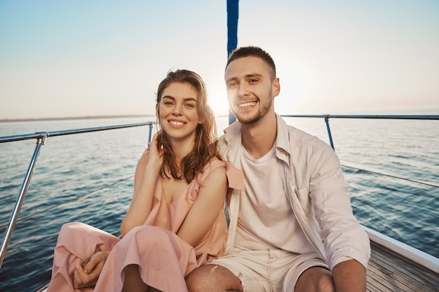 Young european romantic couple smiling while sitting at bow of boat, hugging, enjoying their holidays. two close friends recently became something more to each other Free Photo