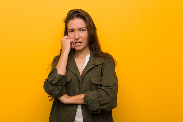 Young european woman isolated over yellow background biting fingernails, nervous and very anxious. Premium Photo