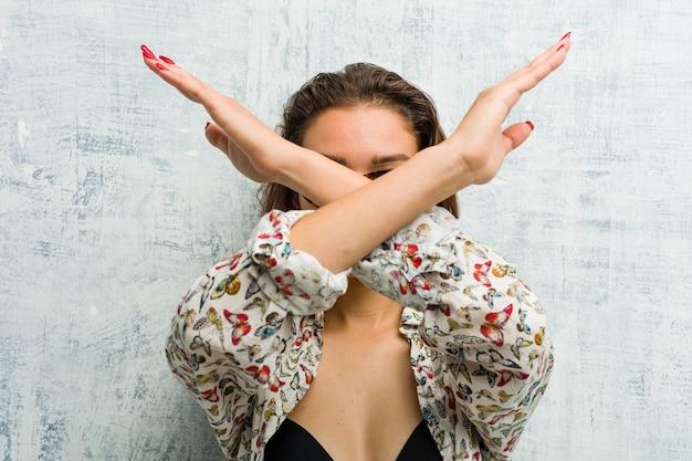 2つの腕を維持するビキニを着ている若いヨーロッパの女性の交差、拒否の概念。 Premium写真