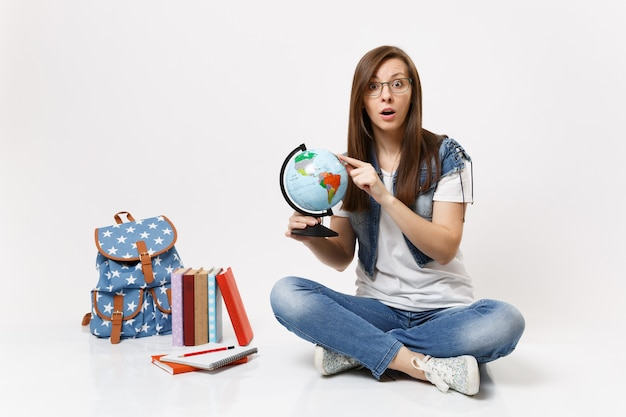 Young excited amazed woman student holding globe pointing index finger on country, place sitting near backpack, school books isolated Free Photo