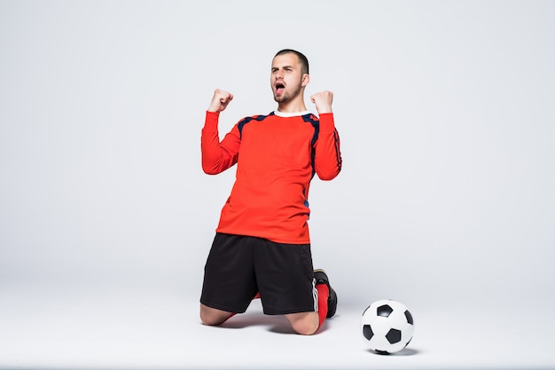 Giovane ed eccitato giocatore di football in maglia rossa che celebra l'obiettivo di segnare Foto Gratuite