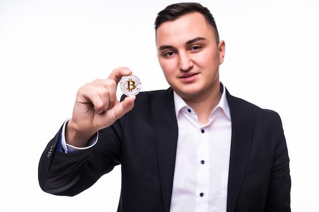 Il giovane uomo eccitato su bianco tiene la moneta bitcoin nelle sue mani Foto Gratuite