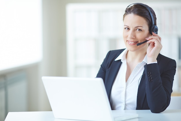 Young executive working with headset and laptop Free Photo