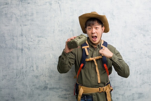 Young explorer chinese man surprised, feels successful and prosperous Premium Photo