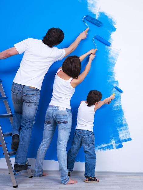 Giovane famiglia che spazzola insieme il muro nel colore blu Foto Gratuite