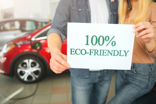 Young family buying first electric car in the showroom. eco car. close-up of hands holding paper with word eco-friendly on battery electric car background. eco technology in the automotive industry Premium Photo