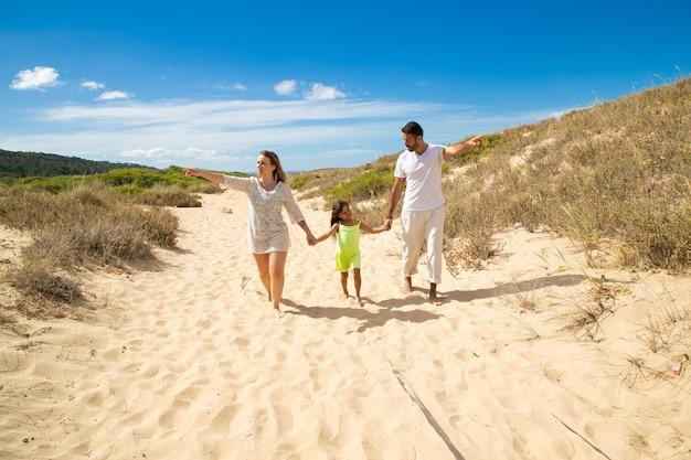 Молодая семейная пара и маленький ребенок в летней одежде гуляют белым по песчаной дорожке, указывая руками в сторону, девочка, держащаяся за руки родителей Бесплатные Фотографии