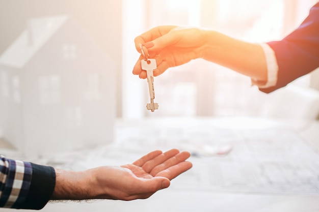 Young family couple purchase rent property real estate . agent giving consultation to man and woman. signing contract for buying house or flat giving keys to couple of customers. close up. Premium Photo