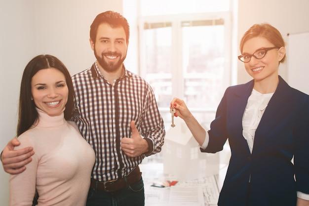 젊은 가족 몇 임대 부동산 부동산을 구입. 남자와 여자에게 상담을 제공하는 에이전트. 주택, 아파트 또는 아파트 구매 계약 체결 고객에게 열쇠를 제공합니다. 프리미엄 사진