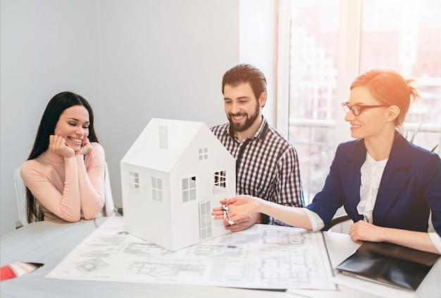 젊은 가족 몇 임대 부동산 부동산을 구입. 남자와 여자에게 상담을 제공하는 에이전트. 주택, 아파트 또는 아파트 구매 계약 체결 그는 집의 모델을 손에 쥐고있다. 프리미엄 사진