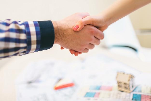 젊은 가족 몇 임대 부동산 부동산을 구입. 남자와 여자에게 상담을 제공하는 에이전트. 주택, 아파트 또는 아파트 구매 계약 체결 악수. 악수 프리미엄 사진