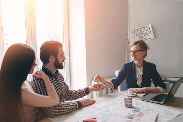 Молодая семейная пара приобретает в аренду недвижимость. агент дает консультации мужчине и женщине Premium Фотографии