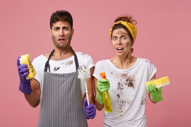 Coppia giovane famiglia con facce sporche che hanno uno sguardo disgustoso che tiene il lavavetri e le spugne che lavano le finestre nel soggiorno. maschio e femmina che completano il loro lavoro sulla casa di cattivo umore Foto Gratuite