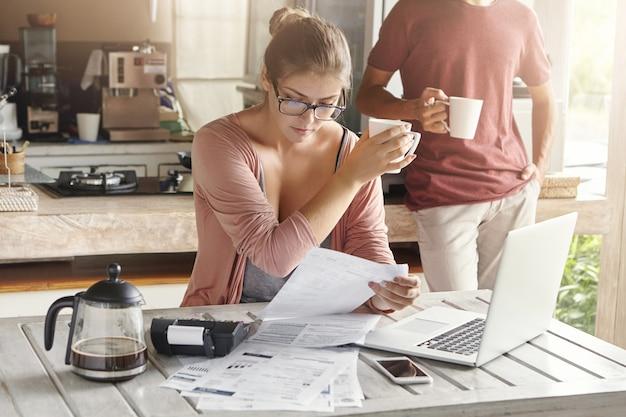 財政問題を扱う若い家族。ラップトップコンピューターの前に座って、請求書を見て、カップを保持している眼鏡の深刻な妻 無料写真