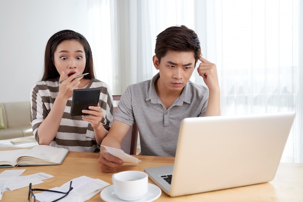 Young family doing family accounting routine stressed by the amount of expenses Free Photo