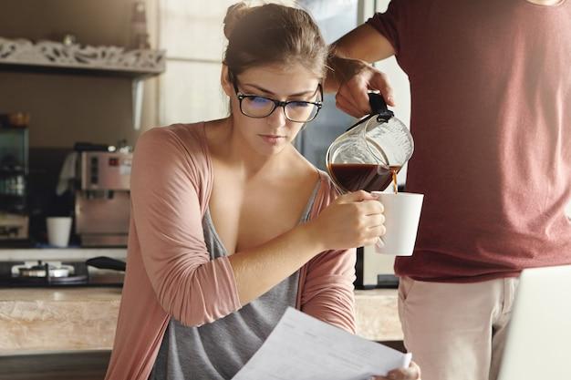 Молодая семья столкнулась с долговыми проблемами. привлекательная женщина в очках читает бумагу из банка с серьезным и разочарованным выражением лица Бесплатные Фотографии