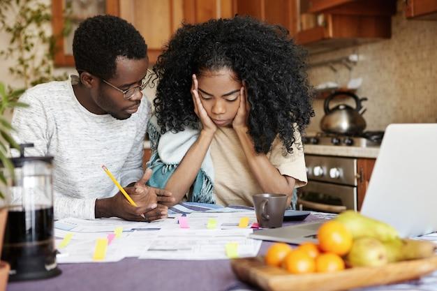 Молодая семья сталкивается с финансовыми проблемами: разочарованная женщина держит руки на щеках, в отчаянии смотрит на бумаги на столе, не выносит стресса, ее муж говорит, что все будет хорошо Бесплатные Фотографии