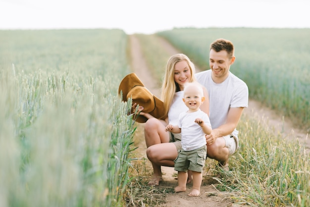 A young family have a fun with their little baby in the field Premium Photo