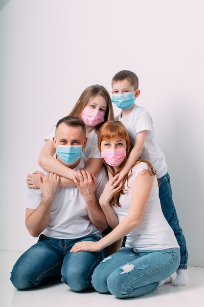Young family in medical masks during home quarantine. Premium Photo
