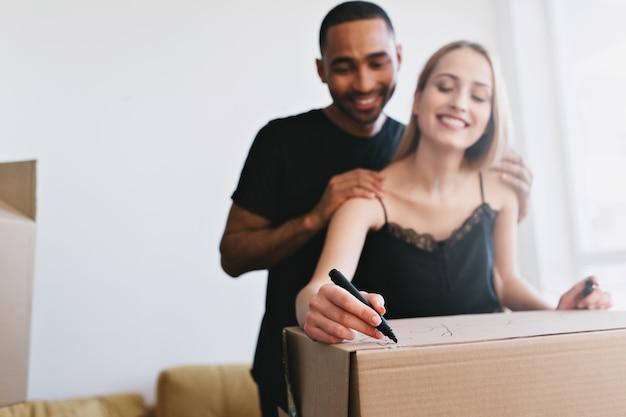 Giovane famiglia che si trasferisce in una nuova casa, acquista appartamento, appartamento. scatole di imballaggio coppia allegra con libri, scrittura di etichette. sono in una stanza bianca con finestra, indossano maglietta e maglietta nera. Foto Gratuite