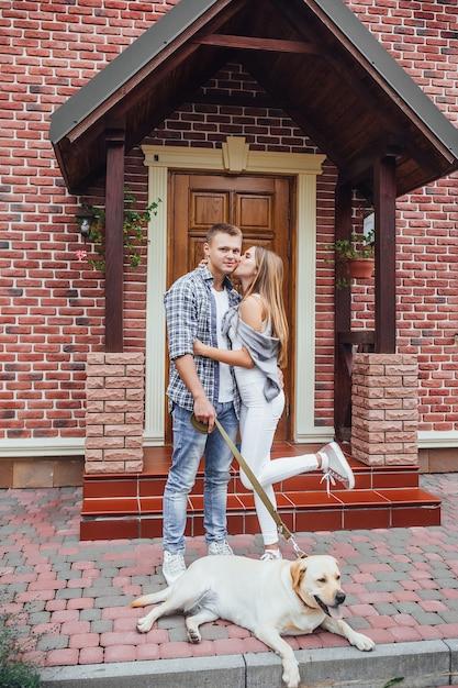 彼らの家の近くの若い家族。大きな家の近くのラブラドールとの魅力的なカップル。 Premium写真