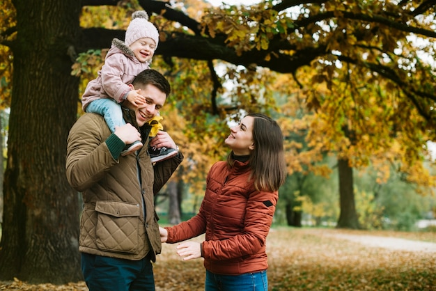 Young family promenading in autumn park Free Photo