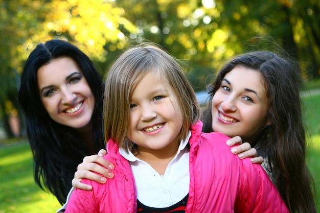 Young family taking healthy stroll through autumn park Free Photo