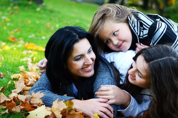 Молодая семья принимает здоровую прогулку по осеннему парку Бесплатные Фотографии