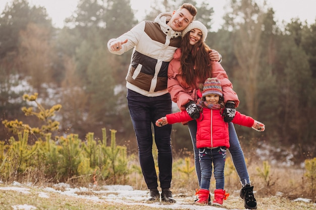 Young family together walking in forest at winter time Free Photo