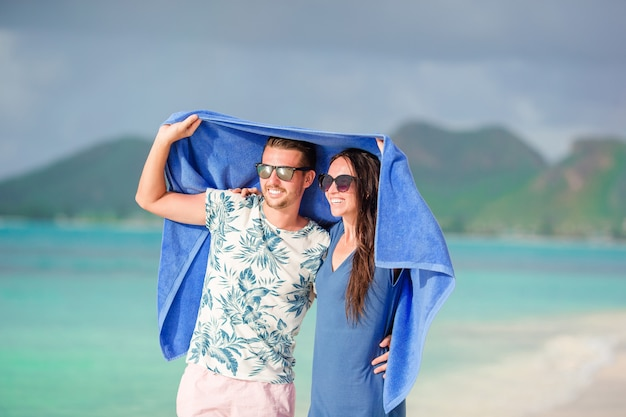 Young family of two at tropical beach with towel. remote tropical beaches and countries. travel concept Premium Photo