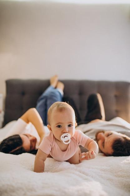 아기 딸 침대에 함께 누워있는 젊은 가족 무료 사진