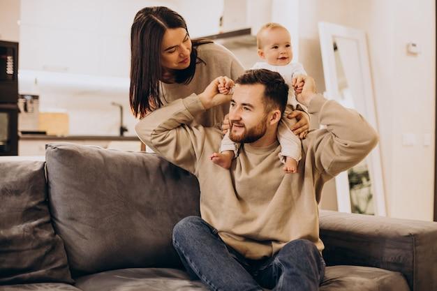 Giovane famiglia con la ragazza del bambino del bambino a casa che si siede sul divano Foto Gratuite