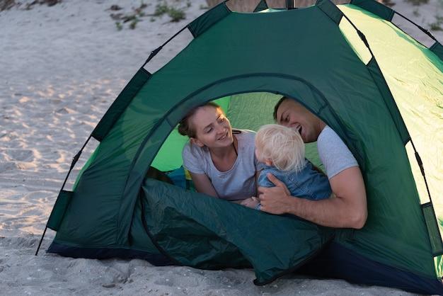 Молодая семья с ребенком в зеленой туристической палатке в кемпинге. отдых с детьми. Premium Фотографии