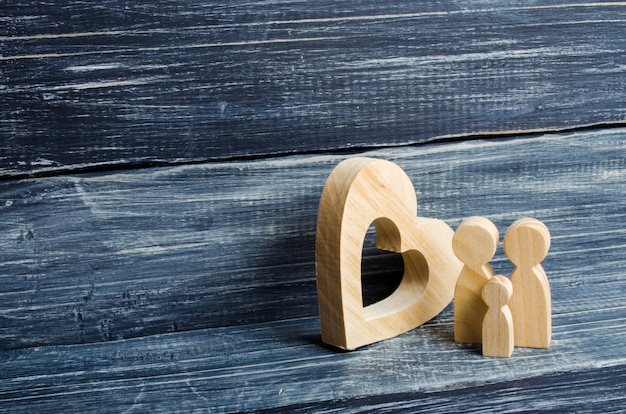 A young family with a child is standing near a wooden heart. Premium Photo