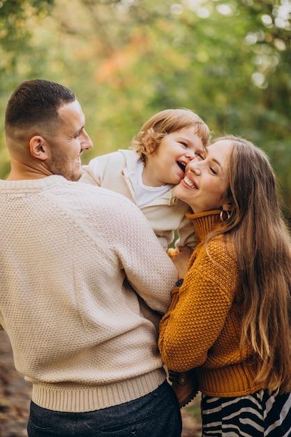 秋の公園で子供を持つ若い家族 無料写真