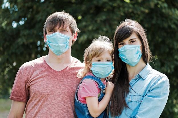 フェイスマスクを着ている娘と若い家族 Premium写真