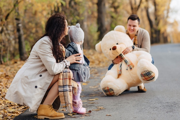 Young family with little daughter at autumn park road present big bear toy Premium Photo