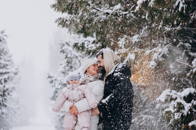 Young family with little daughter in a winter forest full of snow Free Photo